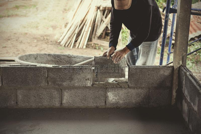 Construction workers are building cement walls with brick blocks stock images