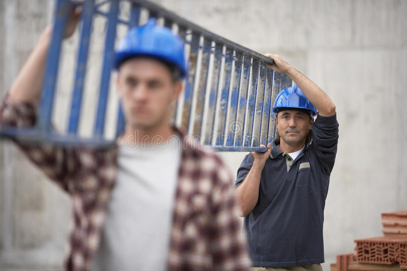 Construction Workers Carrying Ladder royalty free stock image