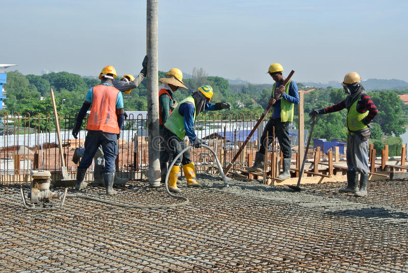 Construction Workers casting concrete using concrete hose. SELANGOR, MALAYSIA – MAY 2014: Construction workers are doing the concrete work using hose from stock image
