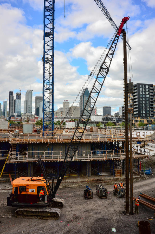 Construction workers erecting steel beam for residential building stock images