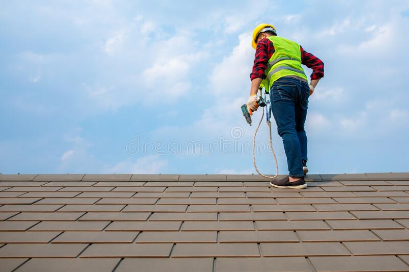 Construction workers Fixing roof tiles, with roofing tools, electric drills used on roofs in safety kits for safety royalty free stock image