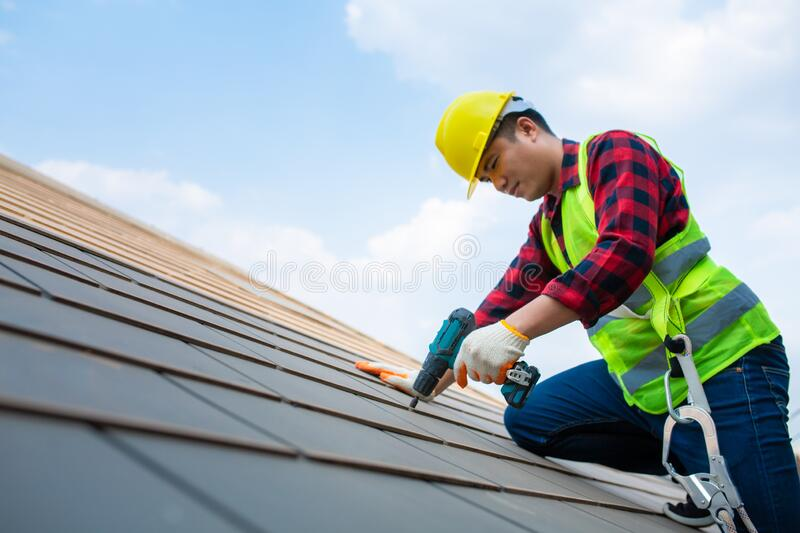 Construction workers Fixing roof tiles, with roofing tools, electric drills used on roofs in safety kits for safety royalty free stock photo