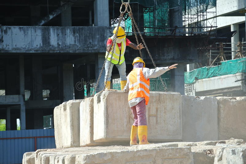 Construction workers hoisting load test block at the construction site stock photography