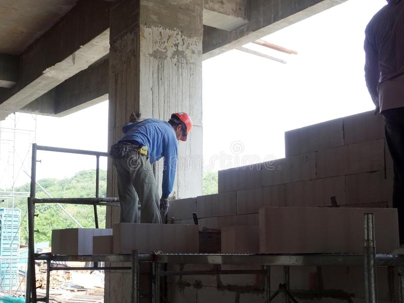 Construction workers installing lightweight block bricks to become wall at the construction site. KUALA LUMPUR, MALAYSIA -MARCH 29, 2017: Construction workers stock images
