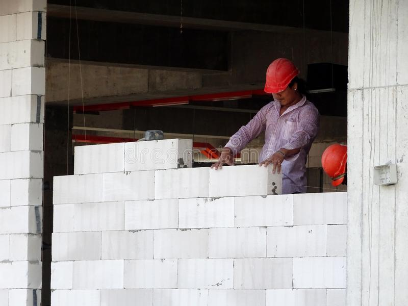 Construction workers installing lightweight block bricks to become wall at the construction site. KUALA LUMPUR, MALAYSIA -MARCH 29, 2017: Construction workers stock photography