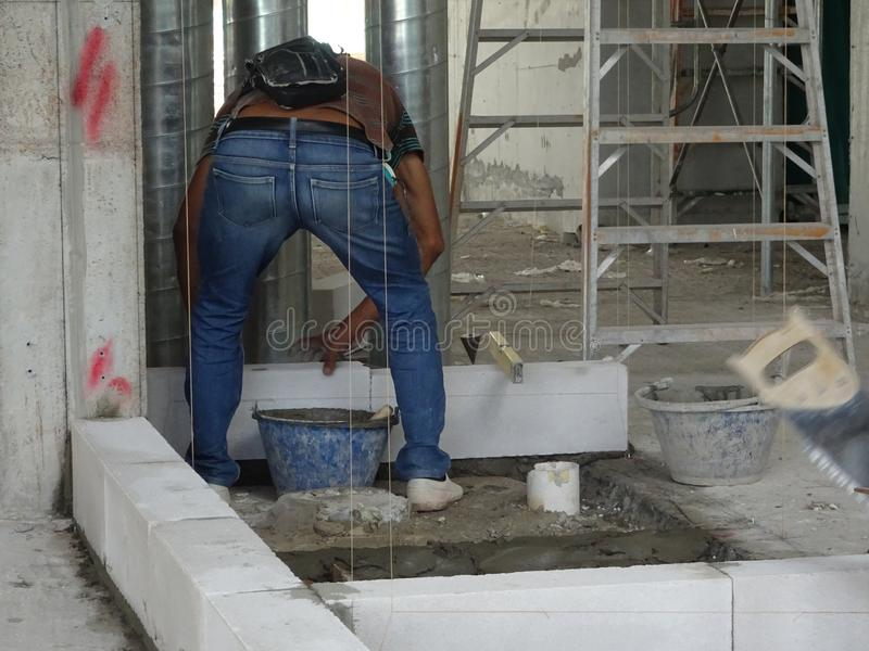 Construction workers installing lightweight block bricks to become wall at the construction site. KUALA LUMPUR, MALAYSIA -MARCH 29, 2017: Construction workers royalty free stock photos