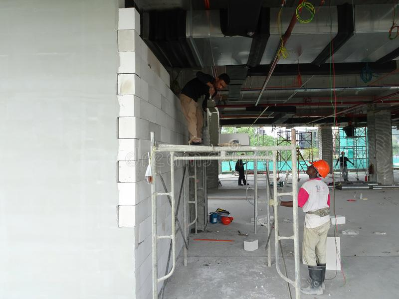 Construction workers installing lightweight block bricks to become wall at the construction site. KUALA LUMPUR, MALAYSIA -MARCH 29, 2017: Construction workers stock photo