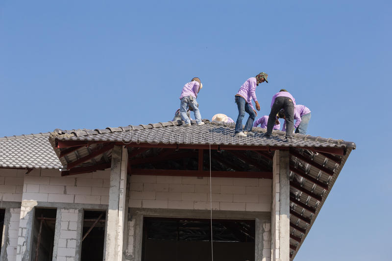 Construction workers installing roof tiles for home building royalty free stock photos