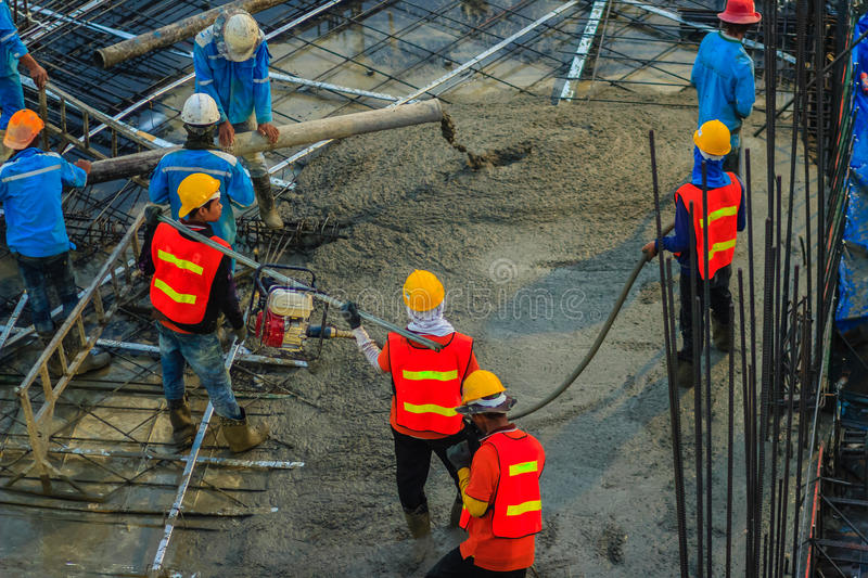 Construction workers are pouring concrete in post-tension flooring work. Mason workers carrying hose from concrete pump or also k stock image