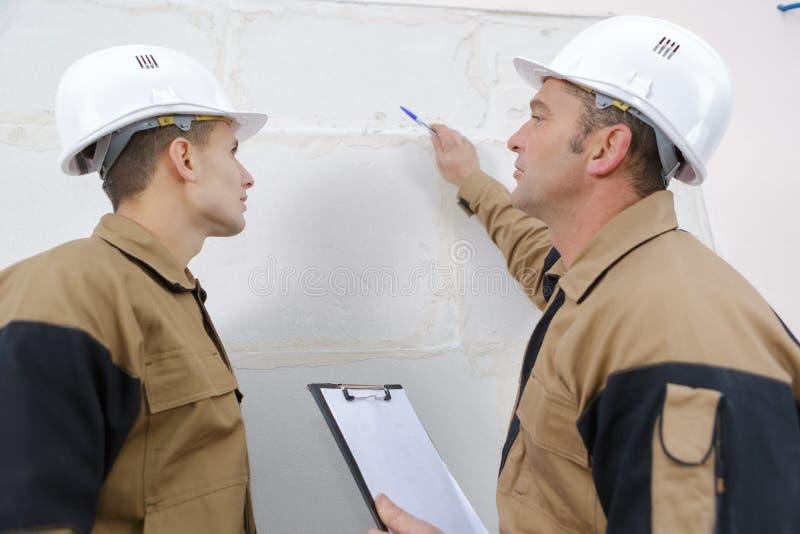Construction workers renovating exterior walls. Builders stock photo