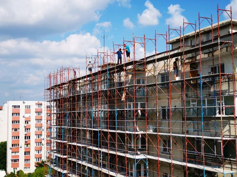 Construction workers on scaffolding - building of flats stock photos
