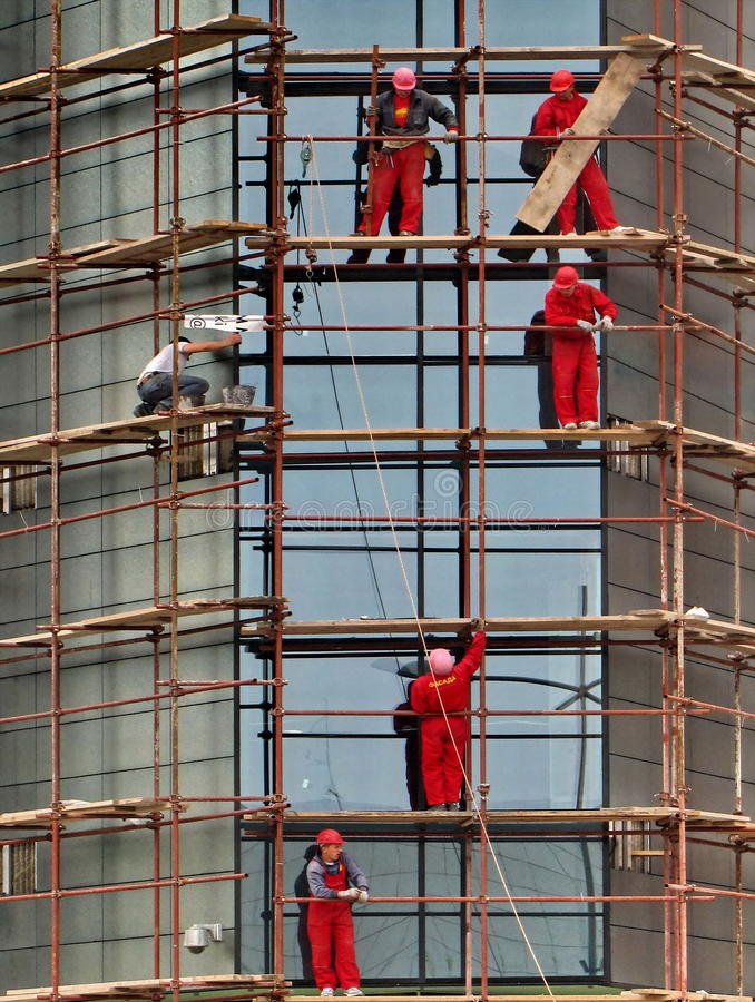 Construction workers on scaffolding. Construction workers working from scaffolding royalty free stock photography
