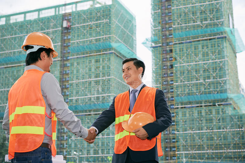 Construction workers shaking hands stock photo image of two vietnamese construction workers greeting each other m4hsunfo Choice Image