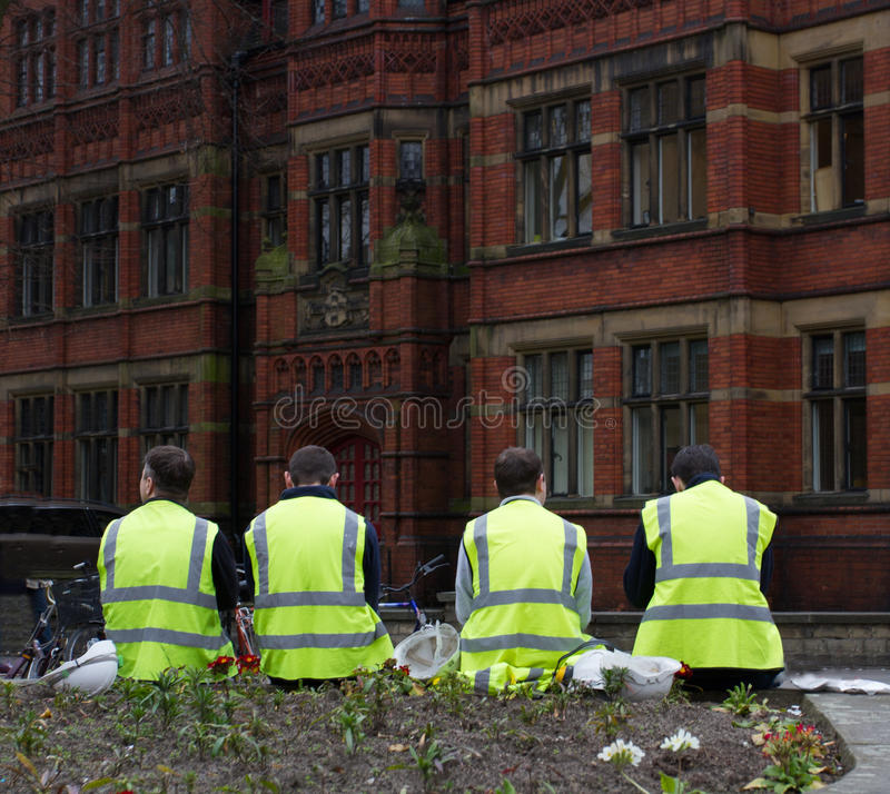 Construction Workers Taking A Break. Construction workers wearing high visibility clothing taking a break outdoors on the city streets of York stock images