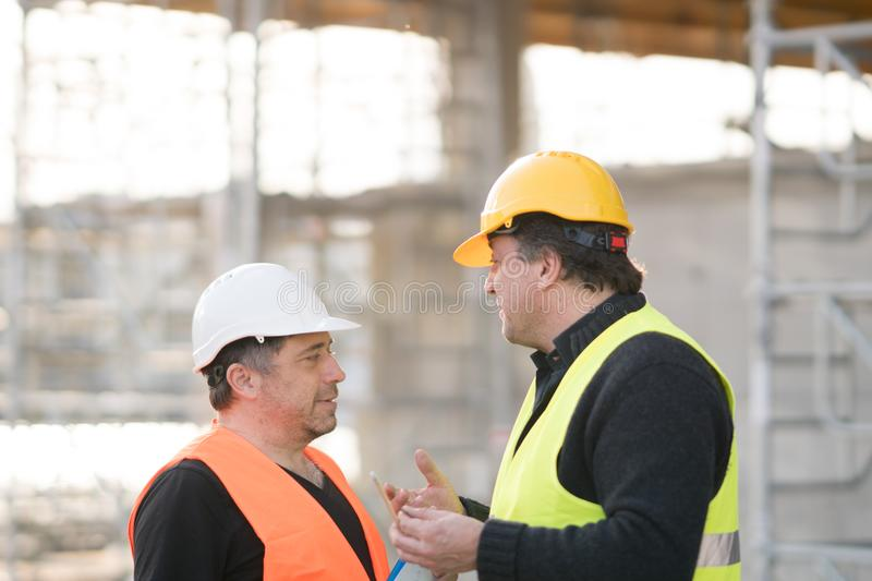 Construction workers talking on construction site royalty free stock photos