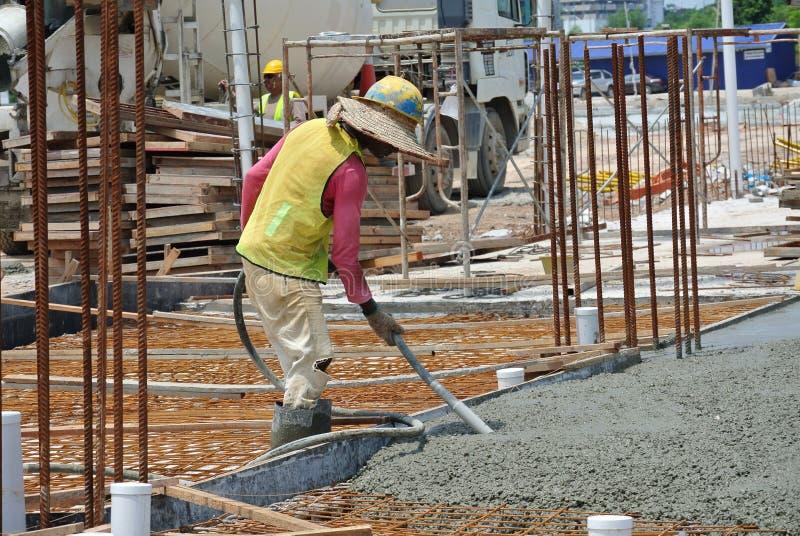 Construction Workers Using Concrete Vibrator. CYBERJAYA, MALAYSIA – MAY 2014: A construction worker using a concrete vibrator at a construction site in stock images