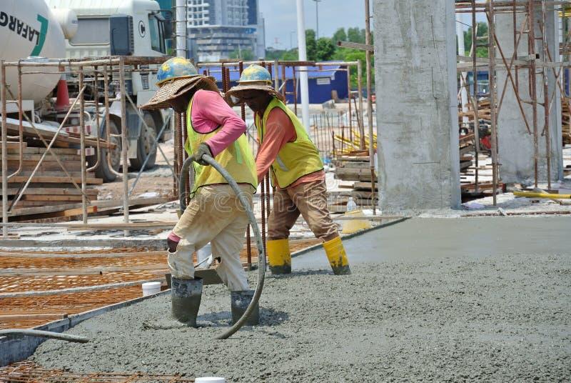 Construction Workers Using Concrete Vibrator. CYBERJAYA, MALAYSIA – MAY 2014: A construction worker using a concrete vibrator at a construction site in stock photo