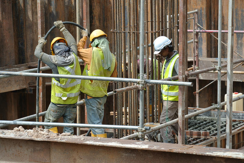 Construction Workers Using Concrete Vibrator to compact the concrete. SELANGOR, MALAYSIA – SEPTEMBER 05, 2015: Construction workers using a concrete stock images