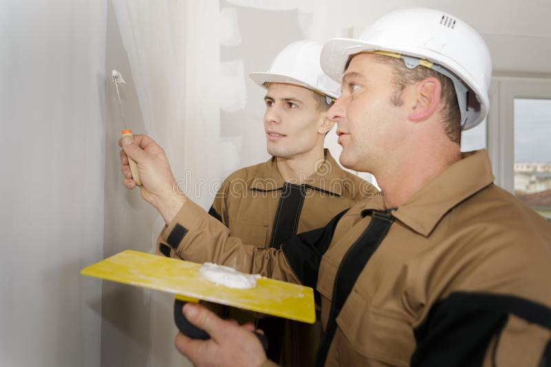 Construction workers with wall plastering tools renovating apartment house. Plasterer stock photos