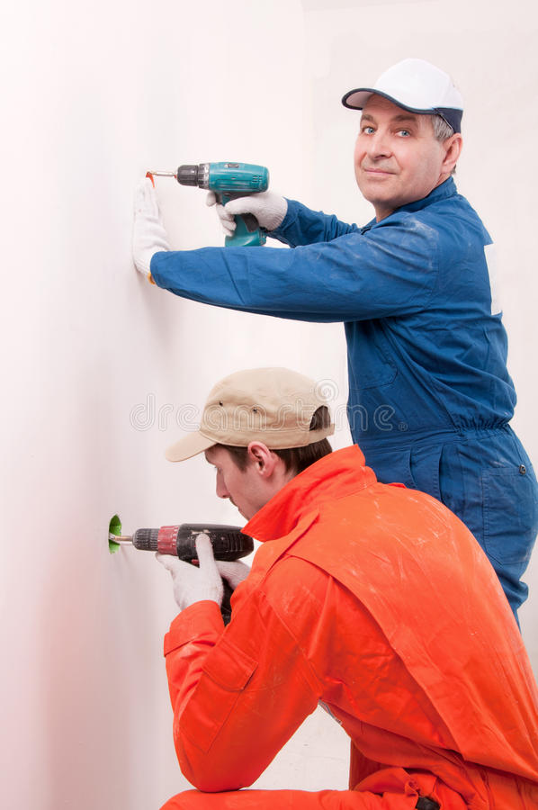 Construction workers at work. Drilling the wall royalty free stock photography