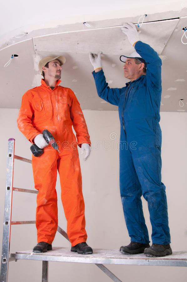 Construction workers at work. Constructing ceiling stock image