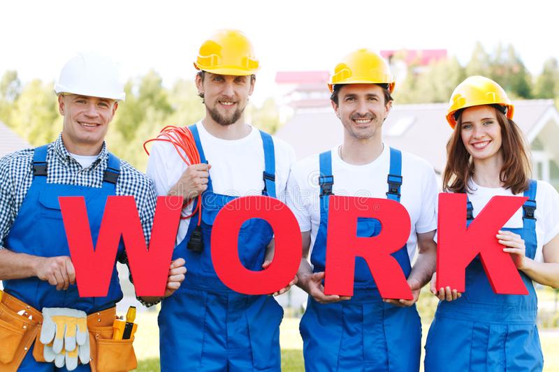 Construction workers with work letters stock image