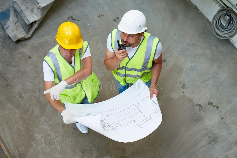 Construction Workers Wrapped up in Discussion royalty free stock photo