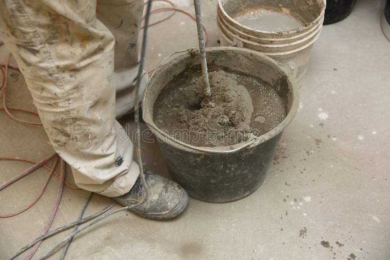 The construction worker mixes tile adhesive together with the water in the correct proportions. Construction works. Mixes adhesive with an electric tool. A stock image
