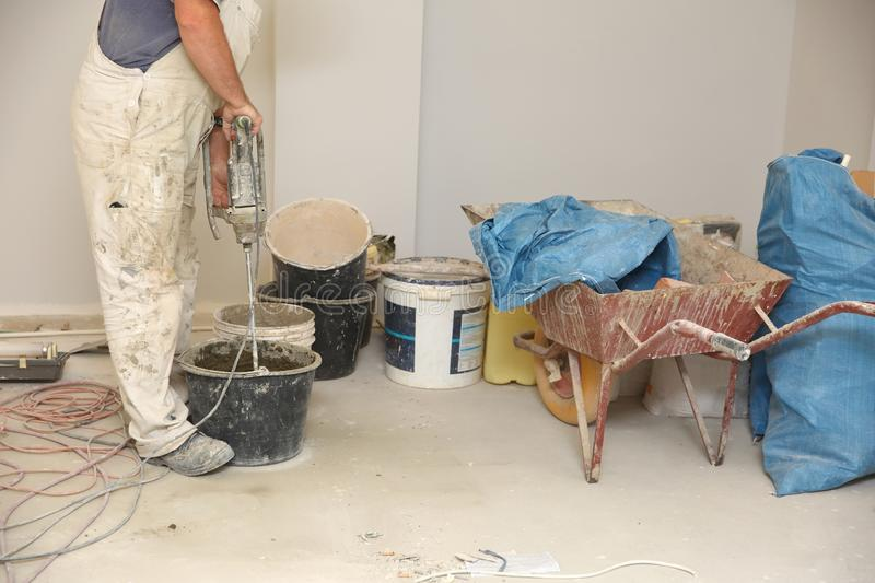 The construction worker mixes tile adhesive together with the water in the correct proportions. Construction works. Mixes adhesive with an electric tool. A stock photo