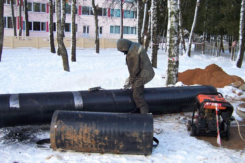 Construction works, the worker does cleaning of a big metal pipe by the electric tool for repair of a heating main, winter, stock photo