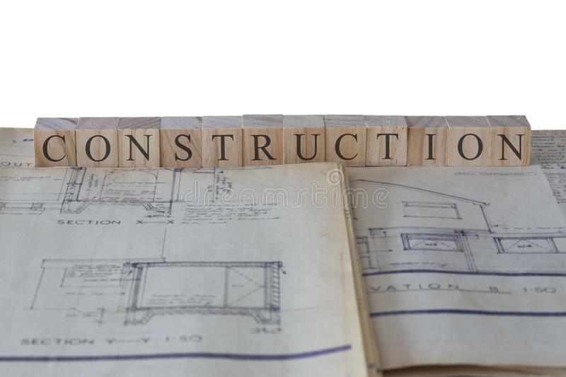 Construction written on wooden blocks on house extension building plans blueprints stock photo