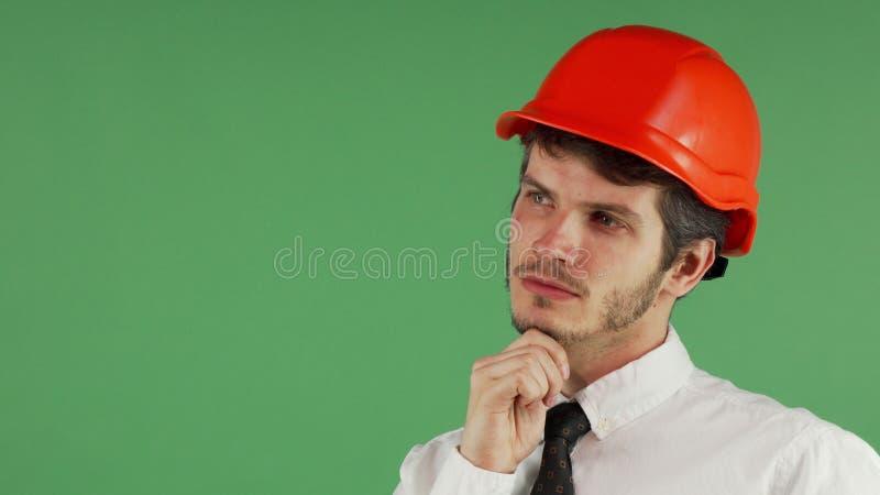 Constructionist maschio bello in un elmetto protettivo che distoglie lo sguardo meditatamente immagini stock libere da diritti