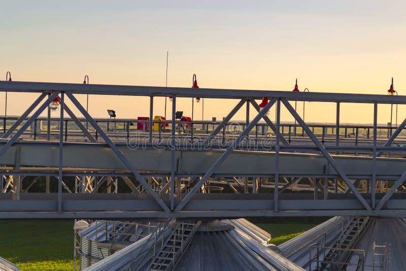 Constructions métalliques de stockage de grain sur le coucher du soleil Backg industriel images libres de droits