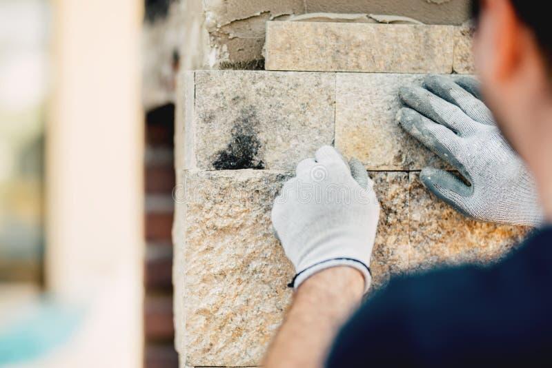 Constructionworker instaluje kamiennej ściany powierzchnię z cementem dla domowy odnawić obrazy royalty free