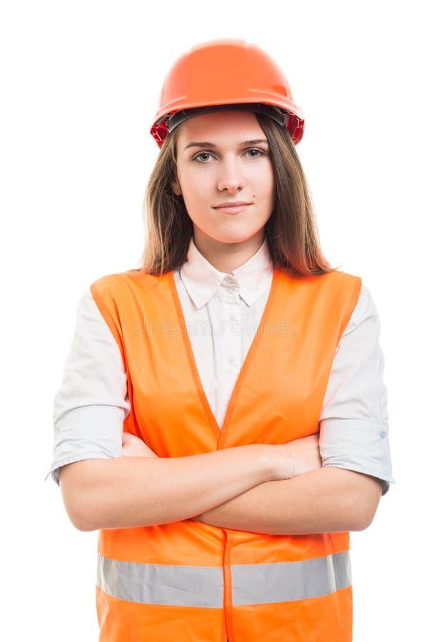 Constructor acertado sonriente de la mujer que presenta con los brazos cruzados fotografía de archivo