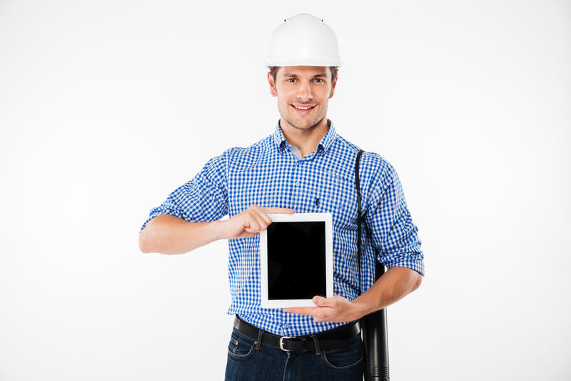 Constructor alegre del hombre en el casco que muestra la tableta de la pantalla en blanco foto de archivo libre de regalías
