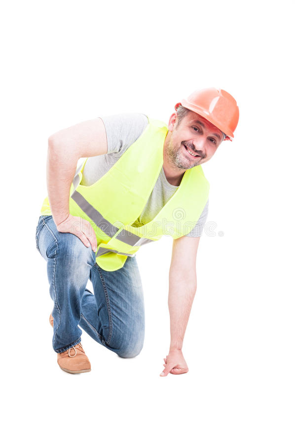 Constructor atractivo sonriente que se arrodilla en el piso foto de archivo libre de regalías