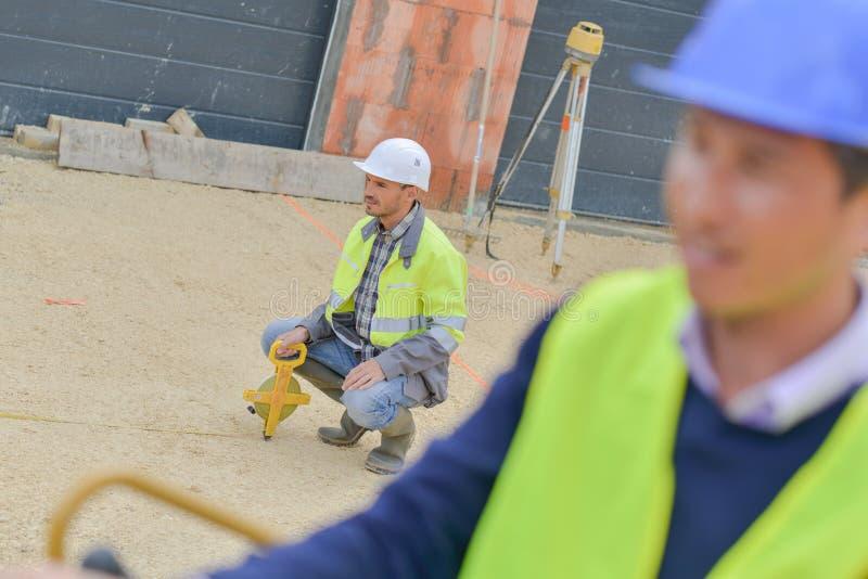 Constructor con el equipo del tránsito del teodolito en el emplazamiento de la obra al aire libre foto de archivo