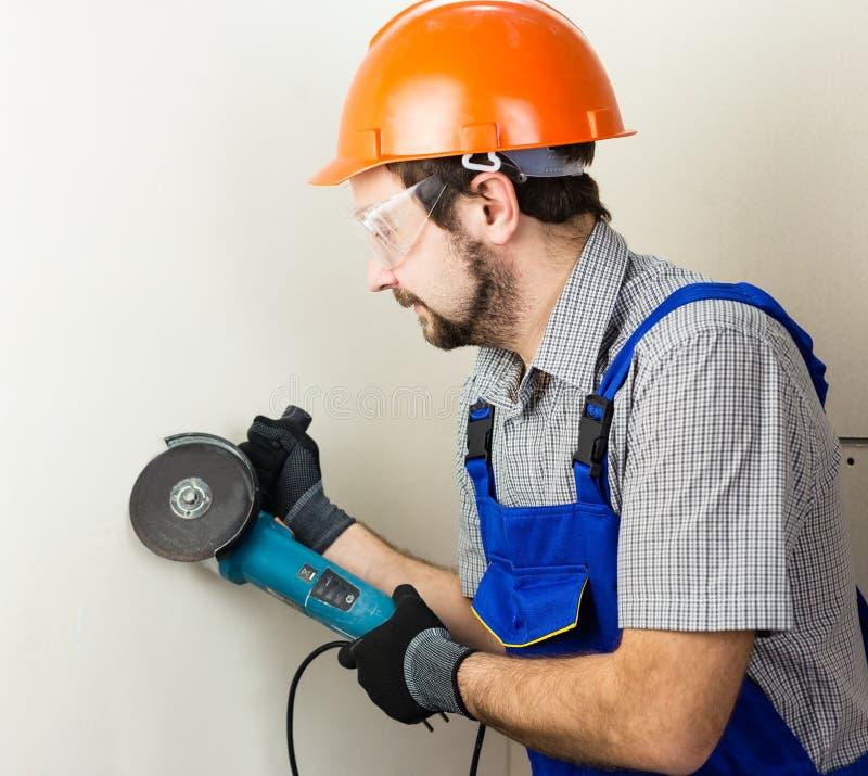 Constructor con una herramienta para el metal en sus manos fotos de archivo libres de regalías