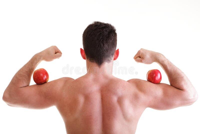 Constructor de carrocería masculina atractivo atlético que sostiene la manzana roja fotografía de archivo