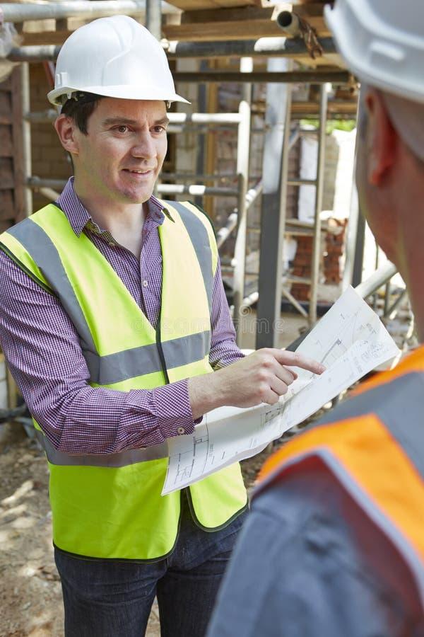 Constructor de Discussing Plans With del arquitecto fotos de archivo