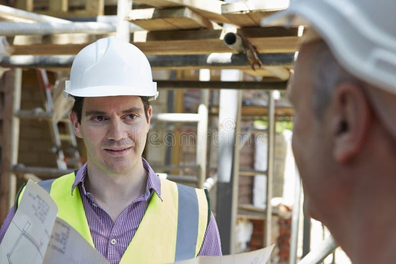 Constructor de Discussing Plans With del arquitecto imagen de archivo libre de regalías