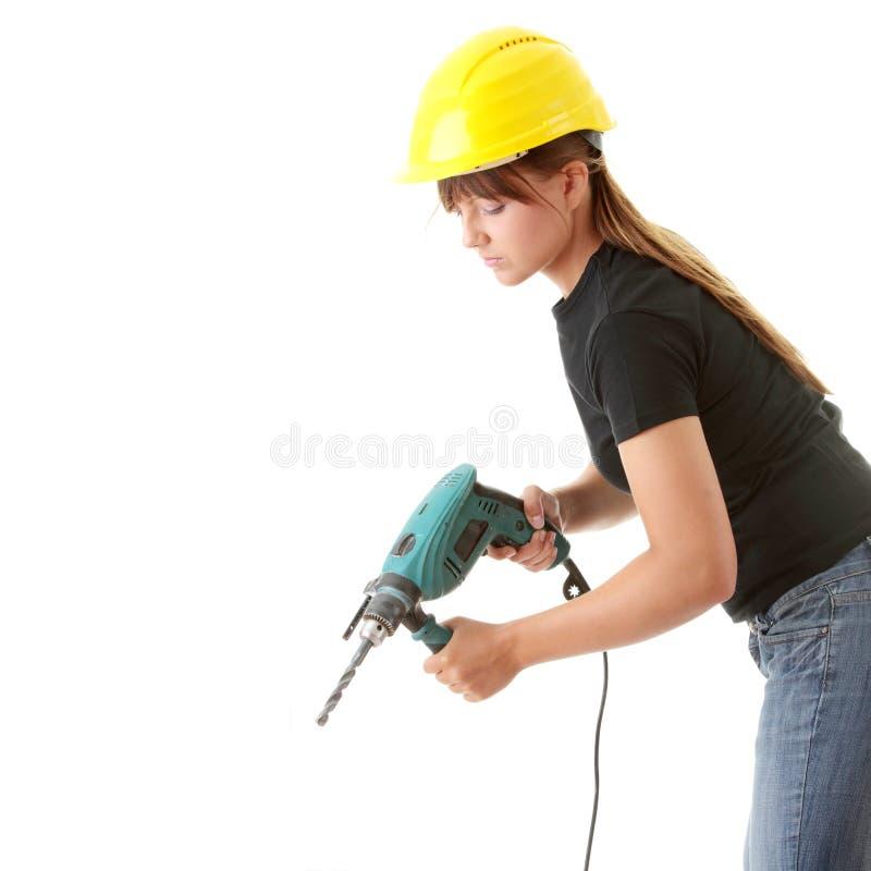Constructor de la mujer joven con la taladradora imágenes de archivo libres de regalías