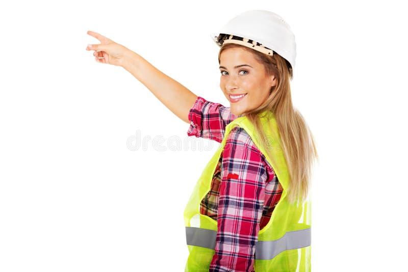 Constructor de sexo femenino joven que señala para algo fotos de archivo