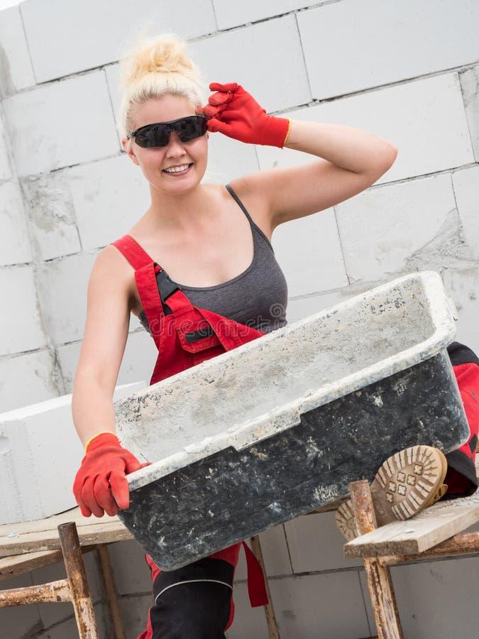 Constructor de sexo femenino que trabaja para construir la nueva casa fotos de archivo