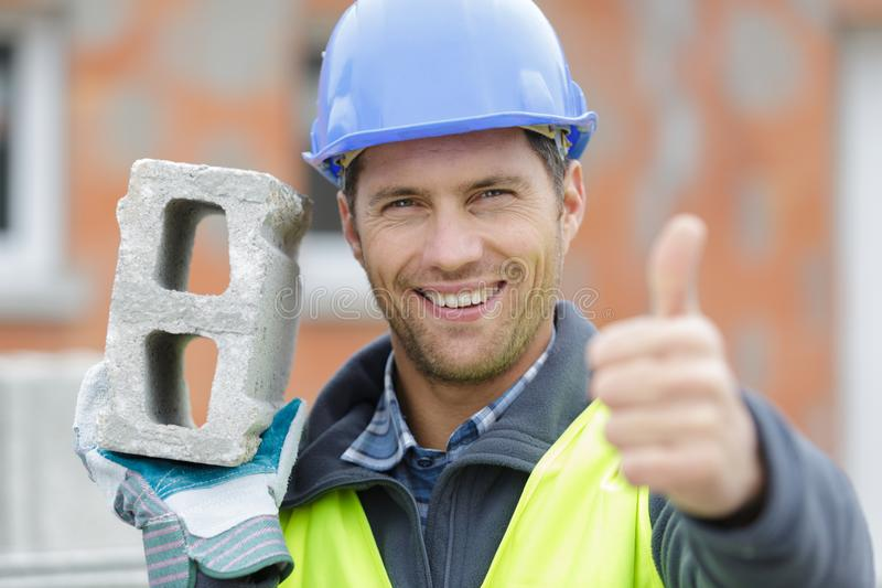 Constructor de sexo masculino feliz que muestra el pulgar para arriba imagenes de archivo