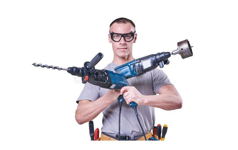 Constructor de sexo masculino que lleva a cabo las manos dos taladros, aislados en el fondo blanco fotografía de archivo libre de regalías