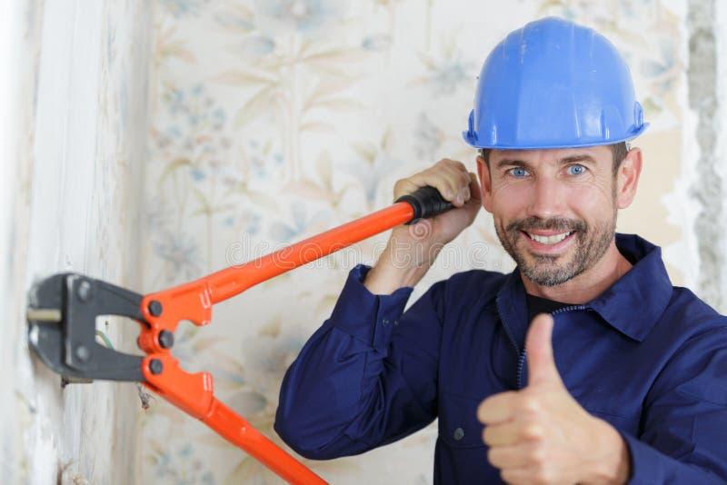 Constructor de sexo masculino que usa al cosechador del perno con los pulgares-para arriba fotografía de archivo