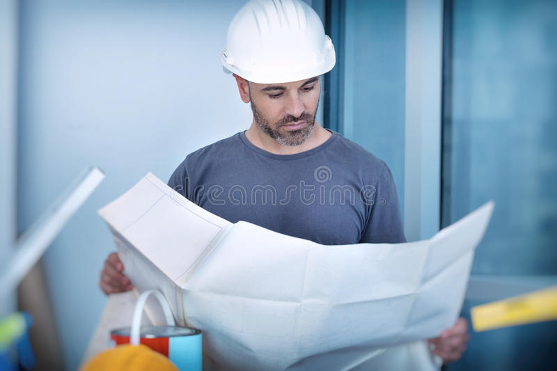 Constructor del arquitecto que estudia el plan de la disposición de los cuartos imagenes de archivo