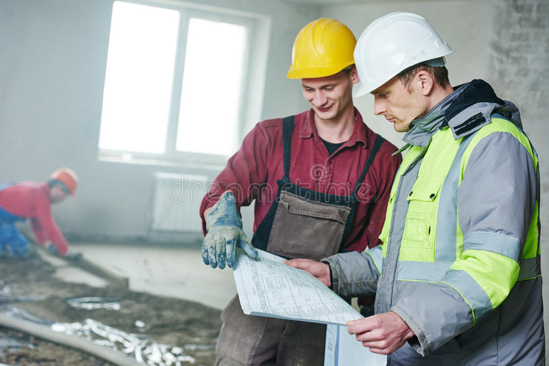 Constructor del capataz y trabajador de construcción con el modelo en el apartamento interior imagenes de archivo